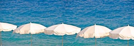 Vita strandparaplyer arrangera i rak linje på havsbakgrund, sommar och turismbegrepp Arkivfoton