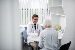 Vita su di medico amichevole che sorride a signora invecchiata immagine stock libera da diritti