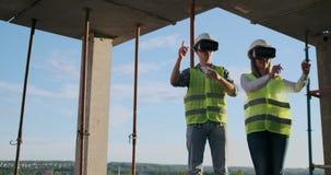 Vita su un ritratto di due muratori moderni che per mezzo dell'ingranaggio di VR per prevedere i progetti sul sito, spazio della  archivi video