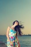 Vita sul colpo delle giovani donne sulla spiaggia con vento Fotografia Stock