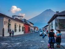 Vita sulle vie dell'Antigua con il vulcano del Agua nei precedenti Immagini Stock