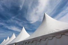 Vita tält mot blå himmel arkivbild