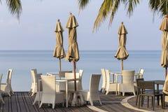 Vita tabell- och rottingstolar i tomt kafé bredvid havsvattnet på stranden, Thailand arkivbilder