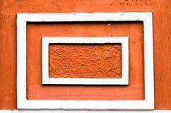 Vita tappningramar på den orange väggen arkivbild