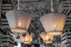 Vita tappningtextillampskärmar av uppochnervända golvlampor som installeras till taket Den sjaskiga chic lampdekoren med snör åt royaltyfria foton