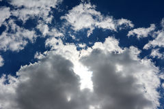 Vita tjocka fluffiga moln på en blå himmel Arkivbild