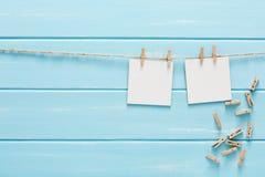 Vita tomma kort på repet, blå träbakgrund Arkivfoto