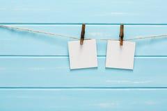 Vita tomma kort på repet, blå träbakgrund Royaltyfria Bilder