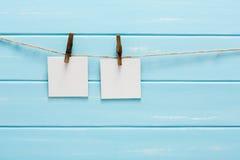 Vita tomma kort på repet, blå träbakgrund Royaltyfri Foto