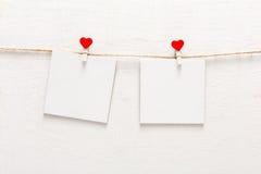 Vita tomma kort på repet, förälskelsemeddelandebakgrund Arkivbild