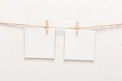 Vita tomma kort på repet, kopieringsutrymme Arkivfoton