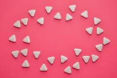 Vita triangulära ovanliga piller sprids i formen av ett ovalt på en rosa bakgrund med copyspace royaltyfria foton