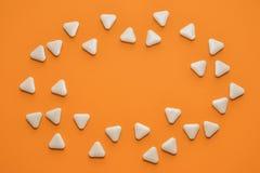Vita triangulära ovanliga piller sprids i formen av ett ovalt på orange bakgrund med copyspace arkivbild
