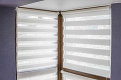 Vita tygrullgardiner på det plast- fönstret med wood textur i vardagsrummet med den blåa väggen arkivfoto