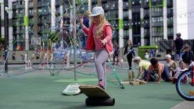 Vita in una città moderna - una ragazza guida un equilibrio-bordo su un campo da giuoco avanzato archivi video