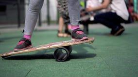 Vita in una città moderna - una ragazza guida un equilibrio-bordo su un campo da giuoco avanzato stock footage