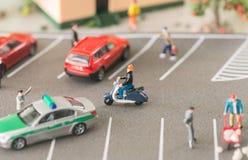 Vita urbana occupata con la gente e le automobili miniatura su una strada affollata fotografia stock