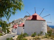 Vita väderkvarnar i rad med Chora, Astypalaia på bakgrunden arkivfoto