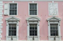 Vita Windows på gammal rosa regerings- byggnad i Bahamas Arkivfoto