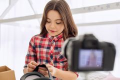 Cute girl showing how to regulate VR headset straps. Vital advice. Lovely pre-teen girl showing how to regulate VR headset straps and recording it on the camera Stock Images