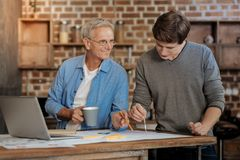 Pleasant mentor helping young colleague draw blueprint. Vital help. Pleasant senior mentor holding a cup of coffee and helping his young colleague draw a stock image