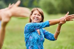 Vital senior woman does a stretching exercise stock photos