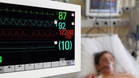 Medical monitor with patient on background in ICU stock video footage