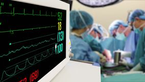 Vital Signs Monitor in hospital surgery room with blur team of surgeons background