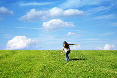 Vitality. Young woman with black hair is running on grass in front of blue sky Royalty Free Stock Photo