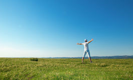 Vitality man on the summer field. With open arms from behind Royalty Free Stock Photo