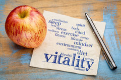 Vitality  word cloud on napkin. Vitality and vital energy word cloud - handwriting on a napkin with a fresh apple Royalty Free Stock Image