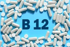 Vitamin B12 text in white capsules frame on blue background. Pill with cobalamin. Dietary supplements and medication royalty free stock image