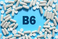 Vitamin B6 text in capsules frame on blue background. Pill with Pyridoxine; Pyridoxal. Dietary supplements and medication. Vitamin B6 text in white capsules royalty free stock image