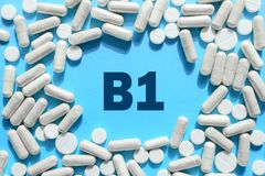 Vitamin B1 text in white capsules frame on blue background. Pill with thiamine, thiamin. Dietary supplements and medication stock photos