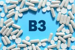 Vitamin B3 text in white capsules frame on blue background. Pill stock images