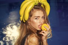 Vitamin in banana at girl near water. woman with tropical fruit in pool. Dieting and healthy organic food. Vegetarian. Summer vacation and travel to ocean royalty free stock photography