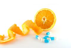 Vitamin C. Orange and blue pills on the white background stock images