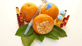 Vitamin C in ampoules, syringe, mandarin, and lime on a light background.Cosmetics Concept