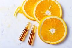 Vitamin C concept. Vitamin C, natural anti aging cosmetics ampulas with oranges stock images