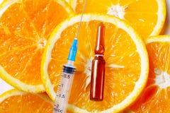 Vitamin C concept. Vitamin C, natural anti aging cosmetics serum and syringe over oranges stock image