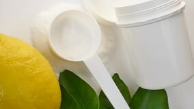 Vitamin C powder. Vitamin C powder in a white plastic spoon and jar, lemon fruit with green leaves on a white background