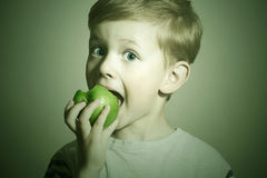 Vitamin.Child eating apple.Little Funny Boy with green apple. Health food. Fruits Royalty Free Stock Photography