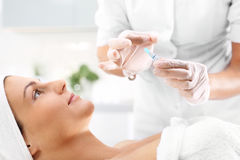 Vitamin cocktail in an ampoule, a woman in the beauty salon. Hand beauticians shows an ampoule with a cosmetic preparation Stock Image