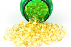 Vitamin D-3 capsules with green pill bottle Stock Photos