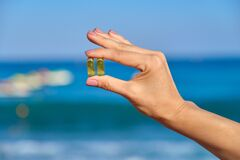 Free Vitamin D, Capsule With Fish Oil In Hand Close-up, Blue Sky Sea Background Royalty Free Stock Image - 188731076
