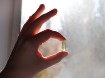 Vitamin D eller omega 3 kapslar Vitaminet stelnar i hand mot fönstret Begreppet av en brist av vitamin D i kroppen arkivfoto
