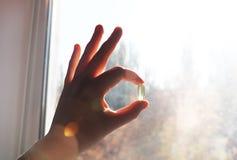 Vitamin D eller omega 3 kapslar Vitaminet stelnar i hand mot fönstret Begreppet av en brist av vitamin D i kroppen royaltyfri bild
