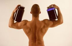 Vitamin diet and sport nutrition. Strong man hold supplement bottles. Eat a healthy diet. Fit man with vitamin. Supplements. Bodybuilding sport and fitness. The stock image
