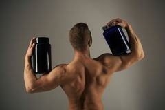 Vitamin diet and sport nutrition. Strong man hold supplement bottles. Muscular man with vitamin supplements. Bodybuilding sport and fitness. Eat a healthy diet stock photo