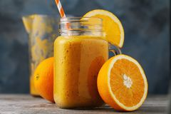 Vitamin drink: smoothies from fresh oranges in a glass jar royalty free stock photo